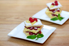 Ptysiowi desery, dekorujący z świeżym malinek, custard i lodowacenia cukierem, tło z kopii przestrzenią Zdjęcia Royalty Free