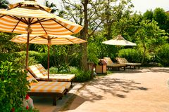 Puści bryczka hole z białymi pasiastymi materac które stoją pod słońce parasolem z ten sam wzorem Sanya, Hainan zdjęcie stock