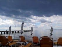 Puści pokładów krzesła na Agia Triada plaży, przedmieście Saloniki, Grecja Pogoda sztormowa, chmury przed burzą obraz stock