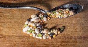 Puñado de legumbres en una tajadera de madera Foto de archivo