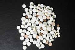Puñado de píldoras en un primer negro del fondo Foto de archivo