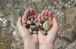 Puñado de piedras en manos Fotografía de archivo libre de regalías
