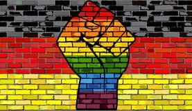 Puño de la protesta de LGBT en una bandera de la pared de ladrillo de Alemania fotos de archivo