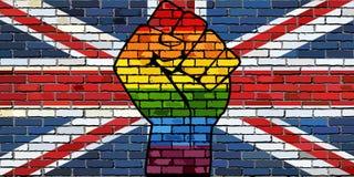 Puño de la protesta de LGBT en una bandera de la pared de ladrillo de Reino Unido foto de archivo