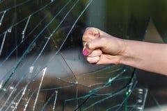 Puño femenino que frena la ventana de cristal Fotografía de archivo