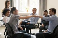 Puño masculino de los colegas que topa en la reunión de grupo que celebra buen t fotografía de archivo