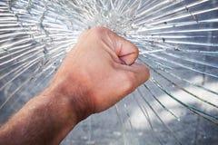 Puño masculino potente con el vidrio quebrado imagen de archivo