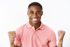 Puños de apretón afroamericanos jovenes emocionados y alegres felices del deportista en la sonrisa de la alegría y de la victoria imagen de archivo