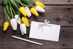 Puści etykietki, ołówkowych i jaskrawych tulipany, kwitną na roczniku drewnianym Zdjęcia Stock