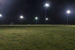 Puści sportowi boisko do piłki nożnej przy nocą z światłami dalej Obrazy Royalty Free