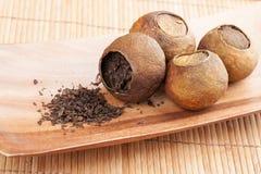 Pu-erh. Chinese tea in dried mandarins. Pu-erh. Chinese tea packed in dried mandarins on wooden table Stock Photos