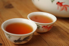 Pu-erh raw tea in small chinese cup with goldfish. Pu-erh or Puer tea (pǔěr chá) is red (also called dark) tea, grown in Yunnan Province of China Royalty Free Stock Photography