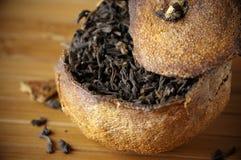 Pu-erh tea aged in tangerine. Close-up of pu-erh tea aged in tangerine on bamboo background Stock Photo