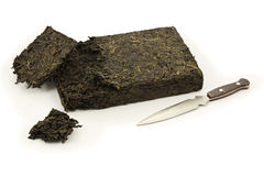Pu-erh tea brick broken by a knife (isolated). Old Pu-erh tea pressed into 250 g brick has been broken into pieces by a Pu-erh knife. The image is isolated on a Stock Photography