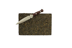 Pu-erh tea brick and a knife (isolated). Old Pu-erh tea pressed into 250 g brick and a knife designed for breaking the brick into pieces. The image is isolated Royalty Free Stock Photos