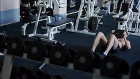 PU joven del atleta, picosegundo su ABS con el peso adicional en un gimnasio con el torso desnudo almacen de metraje de vídeo