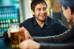 In a pub. Happy men with glass of beer looking at his friend in pub Royalty Free Stock Photos