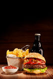 Pub burger meal with fries and beer bottle Royalty Free Stock Images