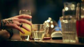 pub Een persoon drinkt alcoholische cocktail van de barteller Een theekop met water die zich op de teller bevinden stock videobeelden