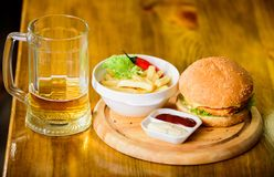 Pub food and mug of beer. Fast food concept. Burger menu. High calorie snack. Hamburger and french fries and tomato. Sauce on wooden board. Delicious burger stock images