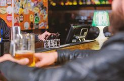 Pub great place to dine drink and have fun. Hipster relaxing at pub. Man spend leisure in dark pub. Man sit at bar. Counter in pub. Weekend lifestyle. Bartender royalty free stock photo