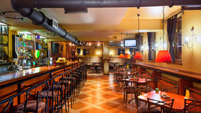 Pub interior. Interior of a modern pub in orange and wooden colors Royalty Free Stock Photos