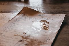 Pub menu with wine and beer stains on a wooden table in an background,beer,black,cafe,dirty,england,english,food,interEnglish pub. Royalty Free Stock Photo