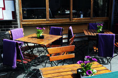 Pub Outdoor Terrace with Purple Flowers. Pub outdoor terrace with wooden tables and chairs, with purple blankets on most of them, for the european cold weather Stock Image