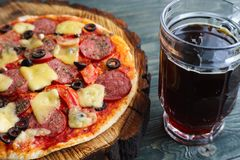 Pub or pizzeria concept. Delicious pizza and mug of dark beer, c. Lose up stock photo