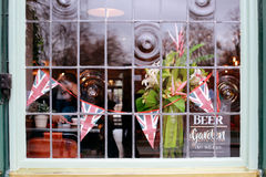 Pub Window. Union Jack decor and interior of traditional English pub, view through the window from outside royalty free stock image