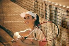 Pubblicità delle racchette di tennis Tennis sorridente felice della donna alla corte Fotografia Stock