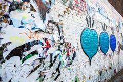 Pubblicità graffiata sulla parete della via come fondo immagini stock