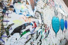 Pubblicità graffiata sulla parete della via come fondo fotografia stock
