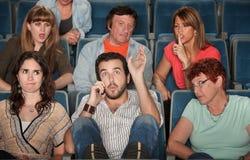 Pubblico arrabbiato con l'uomo sul telefono Immagini Stock