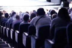 Pubblico che si siede nella disposizione dei posti a sedere a file fotografia stock