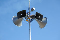 Public address speakers. Photograph of a public address tannoy iaolated on blue sky Royalty Free Stock Photo