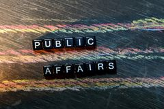 Public Affairs on wooden blocks. Cross processed image with blackboard background. Inspiration, education and motivation concepts royalty free stock photos