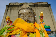 Public ancient head Buddha statue left in the forest for hundred years in wiwekaram temple. Royalty Free Stock Photography