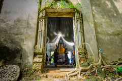 Public ancient Thai Buddha statue left in the forest for hundred years in Wat Somdej temple Royalty Free Stock Photo