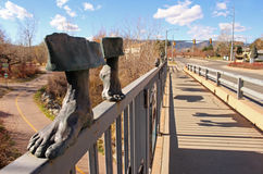 Public art sculpture on bridge railing over bicycle path. Royalty Free Stock Photo