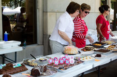 Public bake sale. Ladies cut and serve various baked goods at a charity bake sale Royalty Free Stock Photography