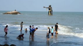 Public beach with monster statue standing in the sea. People enjoy the long white and clean beach infront of the femal monster huge statue created from native Royalty Free Stock Images
