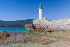 Public beach of Propriano resort town, Corsica. Propriano, France - July 3, 2015: Ordinary people swimming near white lighthouse tower on stone pier. Public Stock Image