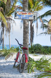 Public beach in Tulum. Hand-painted wooden sign on coconut palm directs visitors to Santa Fe public beach in Tulum, Mexico while a bicycle leans against palm Royalty Free Stock Photo