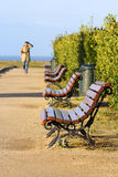 Public bench. Near the ocean, woman in the background Royalty Free Stock Photography