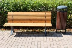 Public bench made of dense narrow wooden boards mounted on stone tiles with metal supports next to similar style public trash can. In front of dense hedge on royalty free stock photo