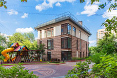Public brown house. With a children's playground next to it Royalty Free Stock Photography