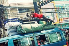 Public bus, Phnom Penh, Khmer, Cambodia. Man riding on top of overcrowded bus in Phnom Penh, Khmer, Cambodia Stock Images