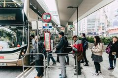 Public Bus station in Hong Kong with line queue of people waiting on the street Royalty Free Stock Image