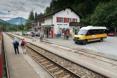Free Public Bus Waits At The Train Station In Versam For The Train To Pass While Many Tourists Walk Around Stock Image - 154688161